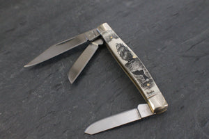 A pocket knife with three blades that nestle into a compact scrimshaw handle made of ethically sourced bone, with an artfully etched Ship and whale tail design. All blades displayed open.