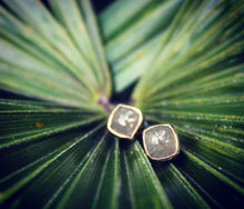 Sea and Stone Jewelry - Stud earrings featuring rose cut grey diamonds bezel set in 14 karat yellow gold. Displayed on a palm leaf.