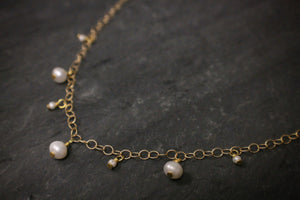 Sea and Stone Jewelry - A Delicate vermeil gold chain necklace with seven petite drop pearls in alternating sizes. Close up.