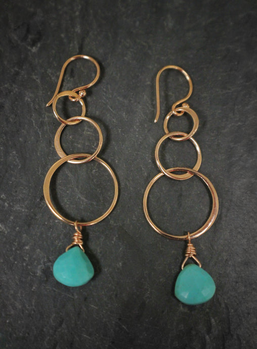 Sea and Stone Jewelry - Drop earrings featuring interlocking rose gold circlets and sleeping beauty turquoise briolettes dangling from hook ear wires