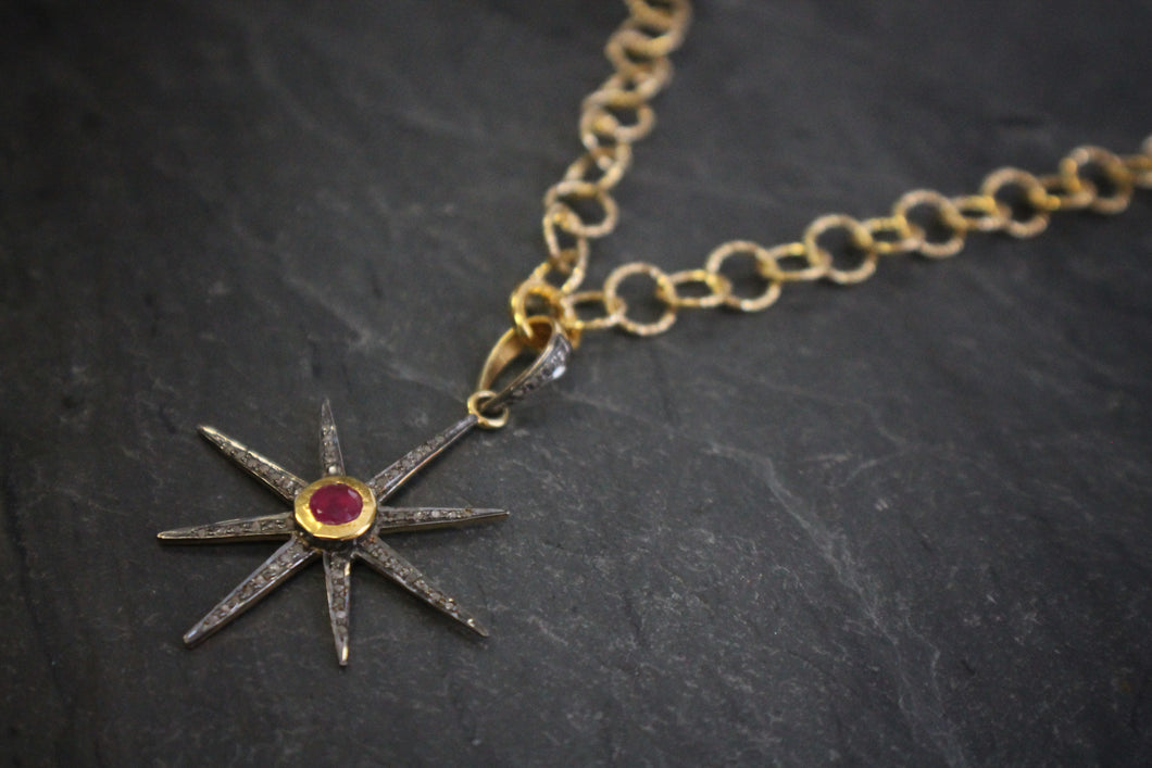 Sea and Stone Jewelry - A gold vermeil starburst pendant set with pave diamonds and a bezel set ruby at the center, hangs from a gold vermeil circle link chain necklace with hammered texture. Close up.