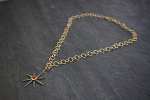 Sea and Stone Jewelry - A gold vermeil starburst pendant set with pave diamonds and a bezel set ruby at the center, hangs from a gold vermeil circle link chain necklace with hammered texture.