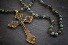 Sea and Stone Jewelry - A brass cross pendant hangs from an African turquoise bead necklace with a gold vermeil clasp. Close up.