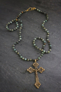 Sea and Stone Jewelry - A brass cross pendant hangs from an African turquoise bead necklace with a gold vermeil clasp.