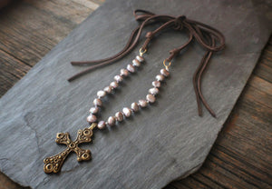 Sea and Stone Jewelry - A brass cross pendant hangs from a lavender pearl bead necklace with gold vermeil components and finished with soft deerskin suede.
