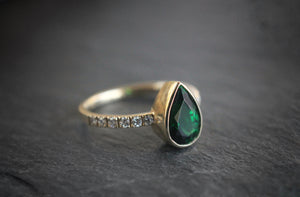Sea and Stone Jewelry - A pear shaped faceted Tsavorite, beautiful emerald colored garnet, stone set in a yellow 14 karat gold ring with diamonds studding the band.