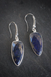 Sea and Stone Jewelry - Drop earrings featuring triangular faceted lapis lazuli stones bezel set in sterling silver, dangling from silver ear wires set with pave white topaz.