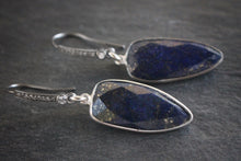 Sea and Stone Jewelry - Drop earrings featuring triangular faceted lapis lazuli stones bezel set in sterling silver, dangling from silver ear wires set with pave white topaz. side view.
