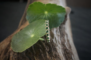 Sea and Stone Jewelry - Bezel ring with 2 millimeter faceted round Tsavorite, beautiful emerald green colored garnet, stones set in 14 karat yellow gold. Displayed held up by leaf.