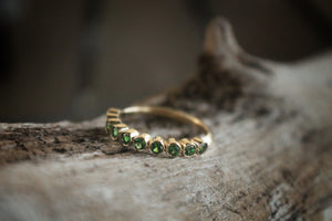 Sea and Stone Jewelry - Bezel ring with 2 millimeter faceted round Tsavorite, beautiful emerald green colored garnet, stones set in 14 karat yellow gold. Displayed on natural wood branch.