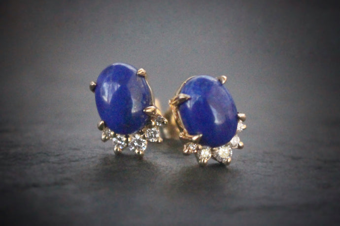 Sea and Stone Jewelry -  Stud earrings featuring lapis lazuli cabochons set in 14 karat yellow gold with a curve of four diamonds underneath. Darker royal blue lapis shown. Close up.