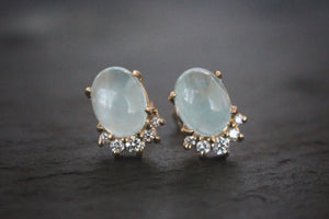 Sea and Stone Jewelry -  Stud earrings featuring aquamarine cabochons set in 14 karat yellow gold with a curve of four diamonds underneath.