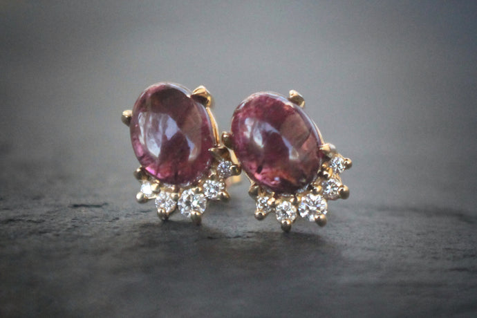 Sea and Stone Jewelry -  Stud earrings featuring pink tourmaline cabochons set in 14 karat yellow gold with a curve of four diamonds underneath. Close up.
