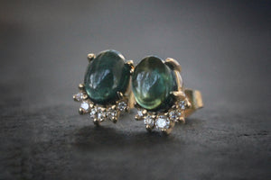 Sea and Stone Jewelry -  Stud earrings featuring green tourmaline cabochons set in 14 karat yellow gold with a curve of four diamonds underneath. Close up.
