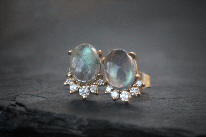 Sea and Stone Jewelry -  Stud earrings featuring labradorite cabochons set in 14 karat yellow gold with a curve of four diamonds underneath. Close up.