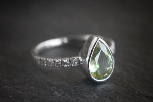 Sea and Stone Jewelry - A pear shaped faceted peridot stone set in a white gold ring with diamonds studding the band. August birthstone.
