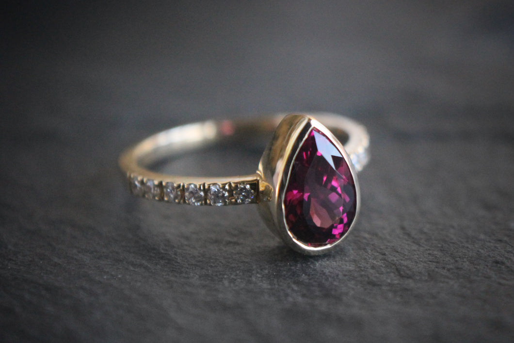 Sea and Stone Jewelry - A pear shaped faceted rhodolite garnet stone set in a 14 karat yellow gold ring with diamonds studding the band. January birthstone.
