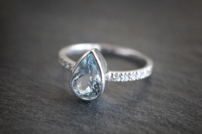 Sea and Stone Jewelry - A pear shaped aquamarine stone set in a white gold ring with diamonds studding the band.