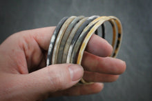 Sea and Stone Jewelry - Set of 7 matte finish horn bangle bracelets being held in hand