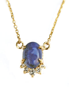 Sea and Stone Jewelry -  A lapis lazuli cabochon pendant, set in 14 karat yellow gold with a curve of four diamonds underneath, hangs from a gold chain necklace.