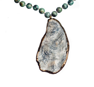 Sea and Stone Jewelry - A gold edged natural oyster shell pendant hangs from an African turquoise bead necklace with gold vermeil clasp. close up.