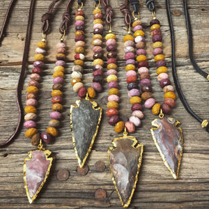 Sea and Stone Jewelry - A gold edged arrowhead style pendant hangs from a natural mookaite bead necklace with deerskin suede ties. Arrowhead color varies.