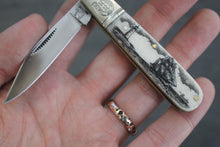 A pocket knife with one blade that nestles into a compact scrimshaw handle made of ethically sourced bone, with an artfully etched ship and lighthouse design. Displayed in hand.