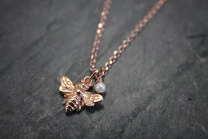 Sea and Stone Jewelry - A dainty rose gold bee pendant embellished with a seed pearl charm, hangs from a rose gold vermeil cable chain necklace.