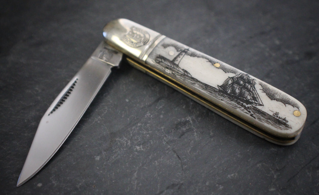 A pocket knife with one blade that nestles into a compact scrimshaw handle made of ethically sourced bone, with an artfully etched ship and lighthouse design.