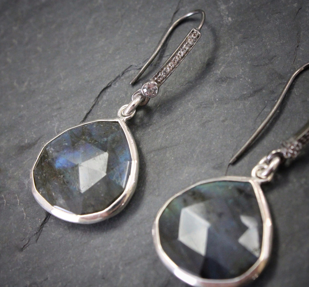Sea and Stone Jewelry - Drop earrings featuring labradorite droplets set into silver under blackened silver hook ear wires set with pave white topaz. Close up