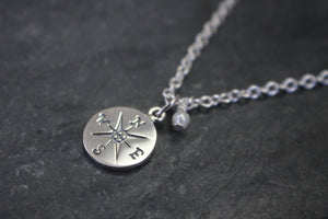 Sea and Stone Jewelry - A sterling silver compass charm pendant, with a tiny pearl embellishment, hangs from a silver chain necklace.