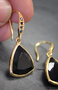 Sea and Stone Jewelry - Drop earrings featuring trillion cut onyx stones set in and hanging under gold vermeil hook ear wires accented with tiny black spinel gemstones. Shown with one being held up.