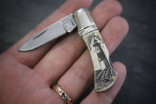 A pocket knife with one blade that nestles into a compact scrimshaw handle made of ethically sourced bone, with an artfully etched lighthouse design. Shown in a hand.