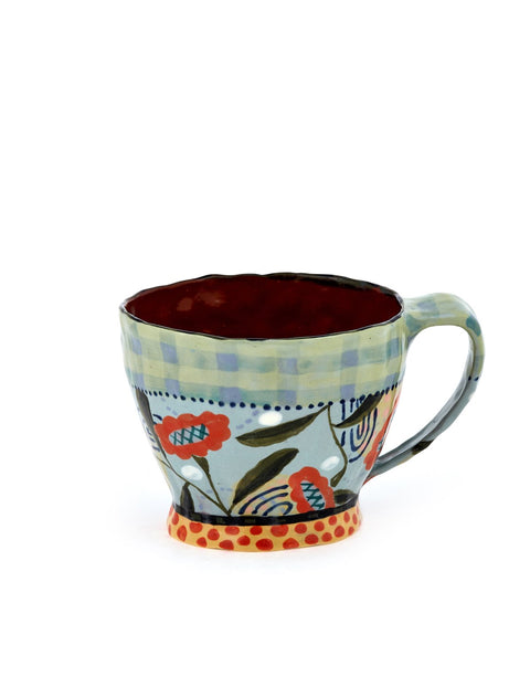 Freeform terra cotta mug with handbuilt handle with turquoise underglaze and botanic surface decoration handmade by artist Nancy Gardner.