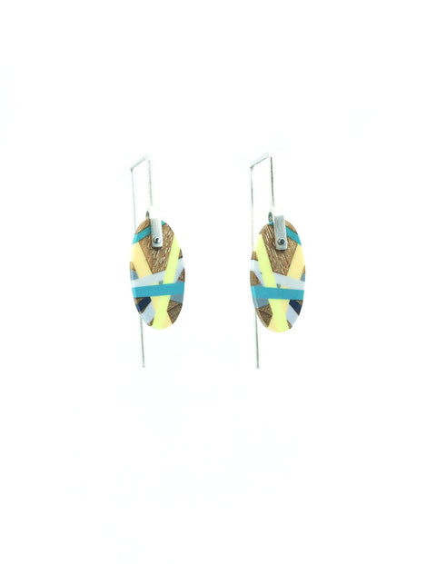 Colorful and unique wood and dyed polyurethane riveted earrings with movement, handmade by Laura Jaklitsch.
