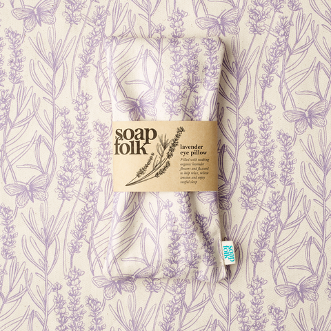 lavender eye pillow resting on organic cotton fabric