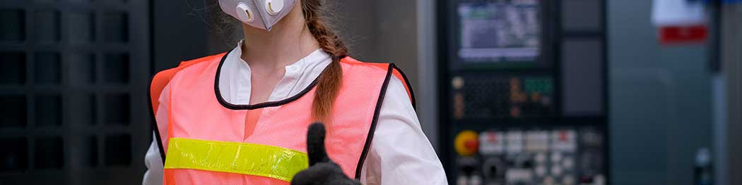 Worker wearing respiratory protection holding thumb up