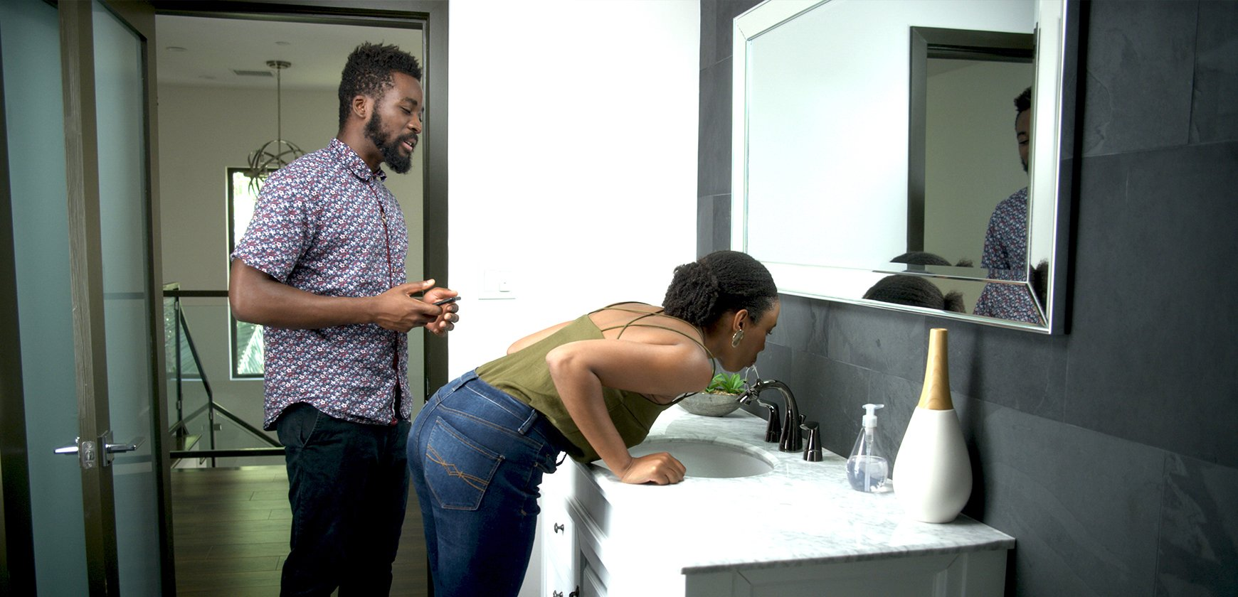 Young couple drinking water from Nasoni Fountain Faucet in modern bathroom