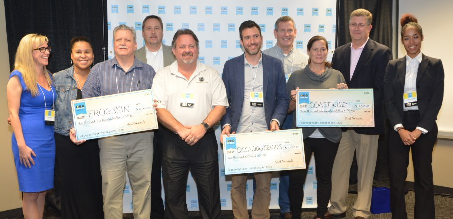 Group of people at event holding large checks