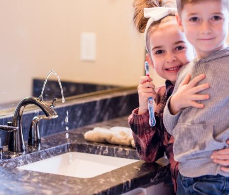 Two children in bathroom brushing their teeth with Nasoni faucet