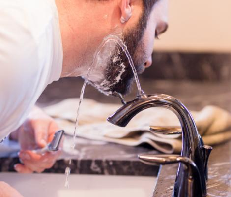 Man shaving beard with Nasoni faucet