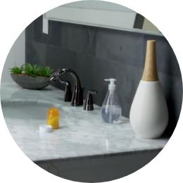 Open pill container on sink countertop near widespread Nasoni faucet