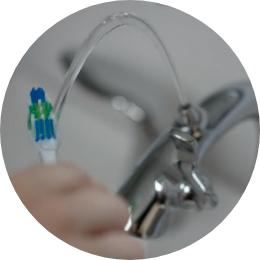 Person holding toothbrush under Nasoni fountain faucet