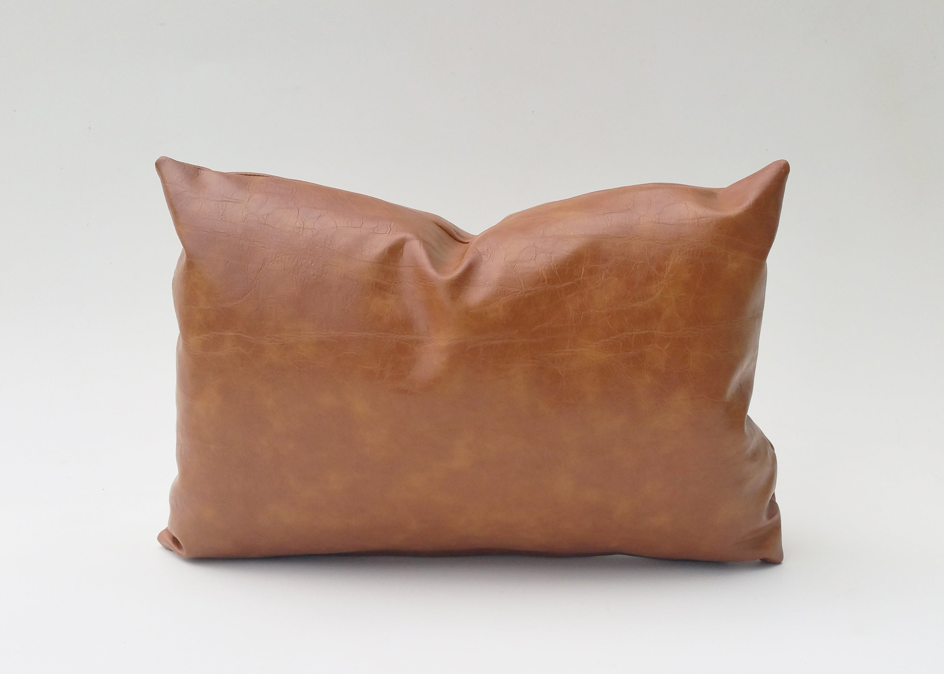 Elizabeth Andersen's classic pillow cover, caramel faux leather adds great texture and a warmth to any space where it's placed. It perfectly transcends all styles and works from living areas to bedrooms to accent chairs or as large floor pillows. This classic throw pillow is available in virtually any size, including custom sizing.