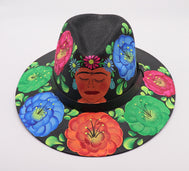 Adult hat uniquely hand painted by local mexican artist. Sombrero hat are comfortable and offer nice shade for summer heat protection and keeping cool. Great cultural piece or gift for a loved one. Each design is unique. Black Hat with black strap and frida flowers painted.