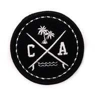 California surf board patch featuring a black circle with embroidered palm trees, surf boards, ocean beach waves, and letters CA. Great addition to sew on to your backpack, jacket, or any fabric. Exclusively sold by SDTrading Co.
