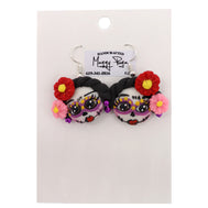 Sugar Skull Earrings for Women. Catrina skull face with braided dark hair and two flowers, large eyes with make-up, and  red lips. Traditional day of the dead earrings made by hand by small shop Maggy Puga. Sold By SDTrading Co.