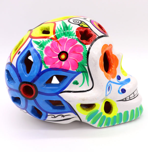Sugar Skulls ceramic clay painted with traditional Mexican art. White traditional catrina skull with multicolor detailed around eyes and flower latten carving. Day of the Dead Catrina. Dia de los Muertos. Skulls decoration.