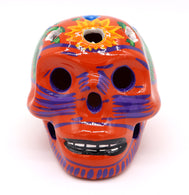 Sugar Skulls ceramic clay painted with traditional Mexican art. Orange with blue stripes on face and sunflower on top with multicolor detailed around flower latten carving. Day of the Dead Catrina. Dia de los Muertos. Skulls decoration.
