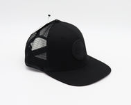 Solid black trucker hat with SD Trading Co Logo in a black Runner Patch in the center
